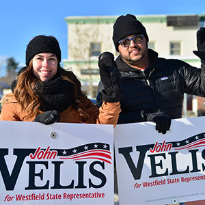 Jazelle and Ryan holding signs for now State Representative John Velis during his Special Election.